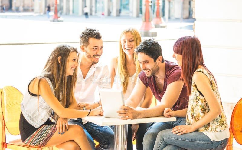坐在餐馆酒吧的朋友小组获得与平板电脑的乐趣-被联络的社区年轻学生人用途便携式 免版税库存照片