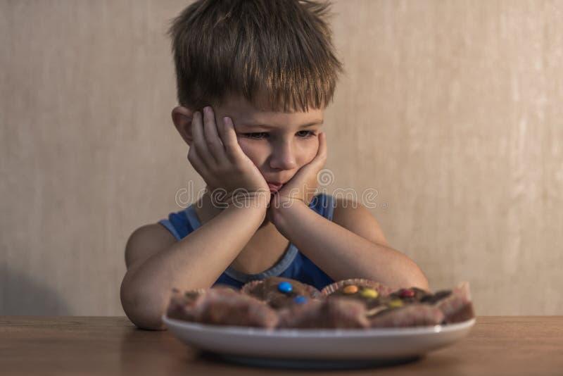 坐在饭桌上的恼怒的小男孩 图库摄影