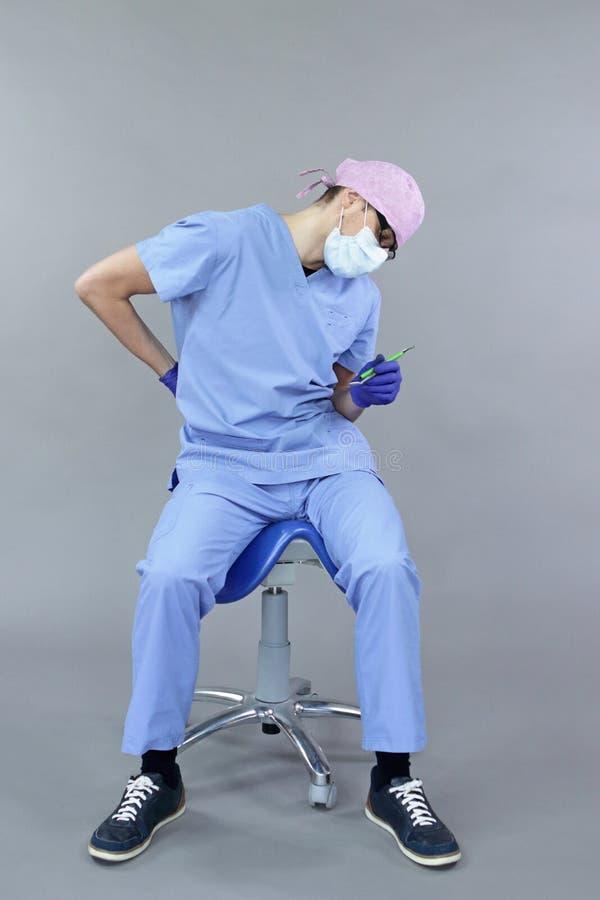 坐在马鞍上的牙医患下背痛 免版税库存照片