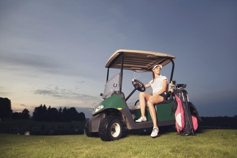 坐在高尔夫车的高尔夫球运动员在微明。 库存图片