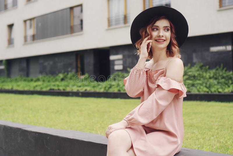 坐在高层建筑物附近的一件桃红色礼服的美女 女孩由电话讲话 有桃红色头发的妇女在黑帽会议 图库摄影
