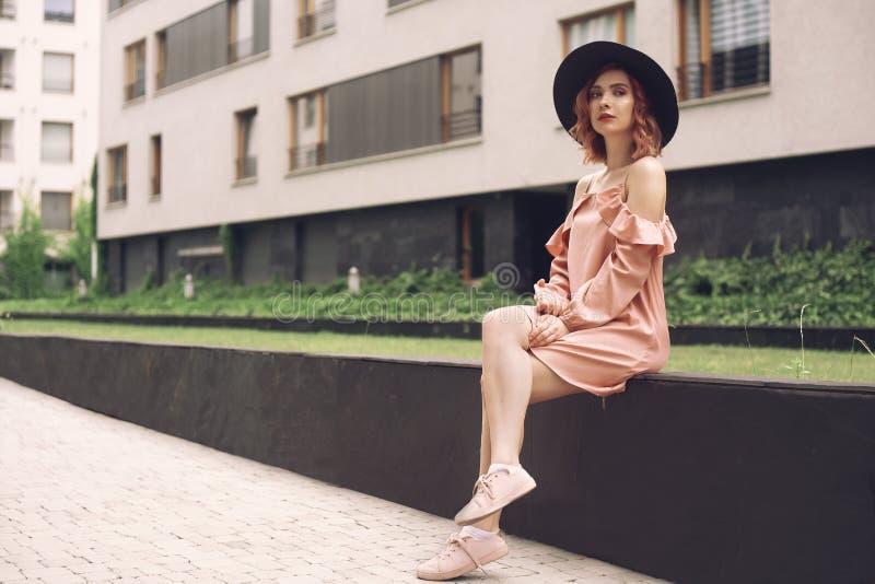 坐在高层建筑物附近的一件桃红色礼服的美女 有桃红色头发的妇女在有电话的黑帽会议 ??i 免版税图库摄影