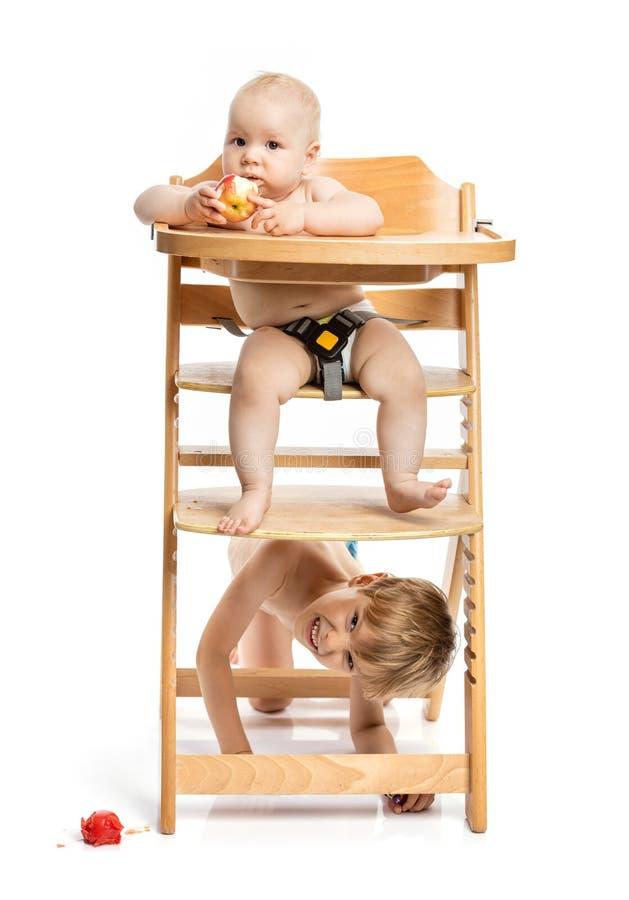 坐在高脚椅子和吃苹果,学龄前男孩的女婴 免版税图库摄影