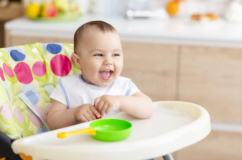 坐在高脚椅子的愉快的婴孩在厨房里 免版税图库摄影
