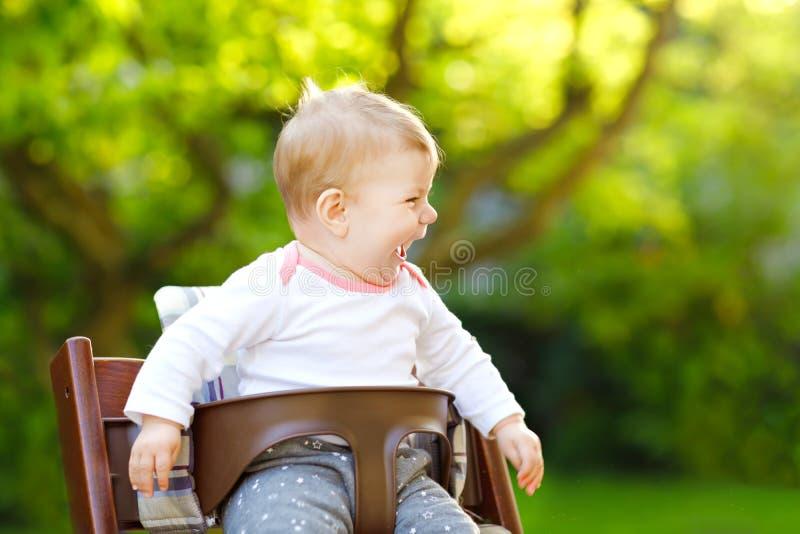 坐在高脚椅子的逗人喜爱的可爱的女婴户外 6个月的Beatuiful孩子在家庭菜园的,使用在温暖 免版税库存照片