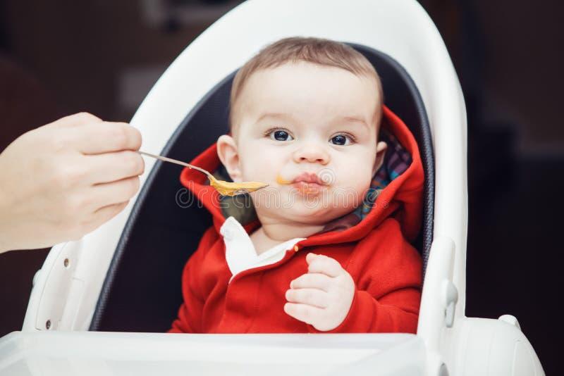 坐在高脚椅子的逗人喜爱的可爱的白种人矮小的男婴画象在吃膳食纯汁浓汤的厨房里 库存图片