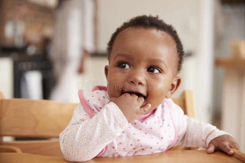 坐在高脚椅子的逗人喜爱的女婴佩带的围嘴 免版税库存图片