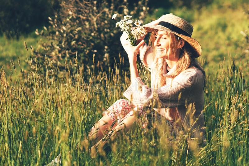 坐在高草的一个provencal样式和草帽的愉快的白肤金发的女孩 库存图片