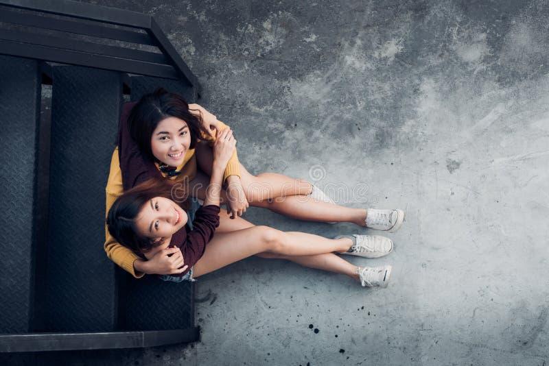 坐在黑屋顶台阶h的两对女性女同性恋的lgbt夫妇 免版税库存照片