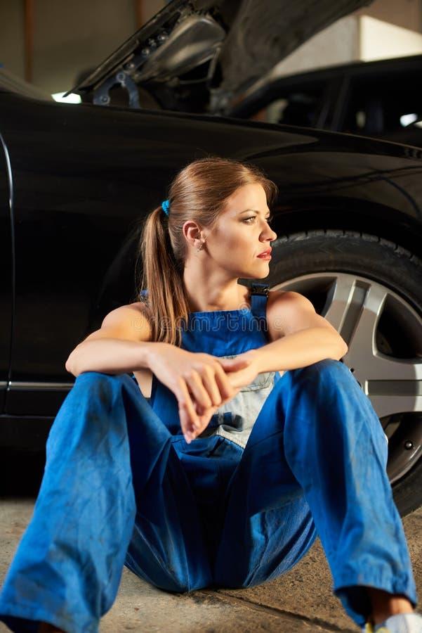 坐在黑汽车附近的年轻女性技工 库存图片