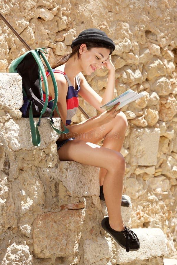 坐在读书地图之外的年轻女性旅客 免版税库存图片