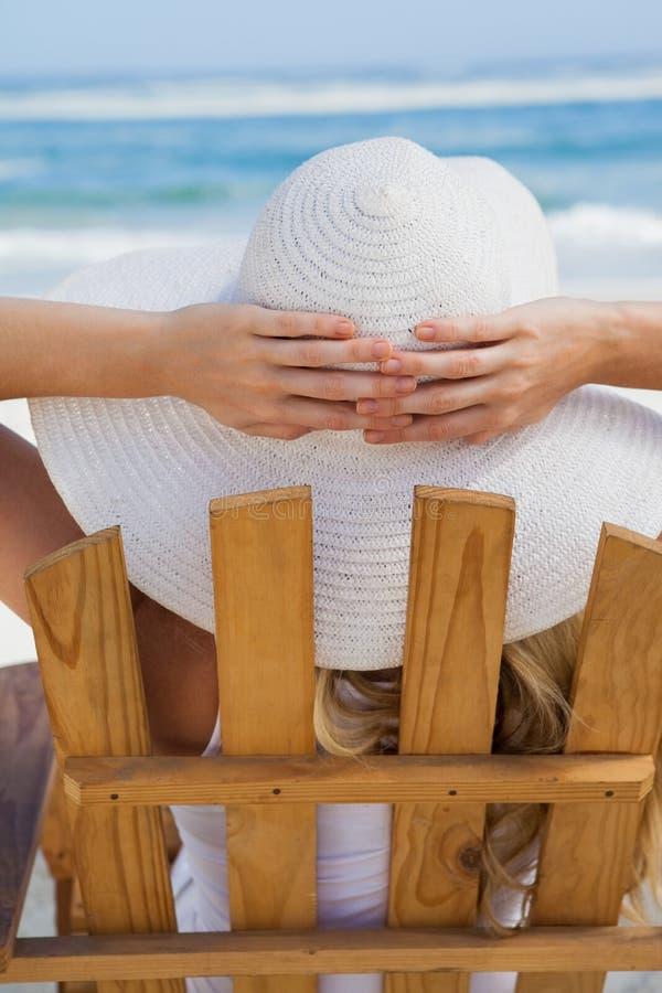坐在轻便折叠躺椅的妇女在海滩 库存照片