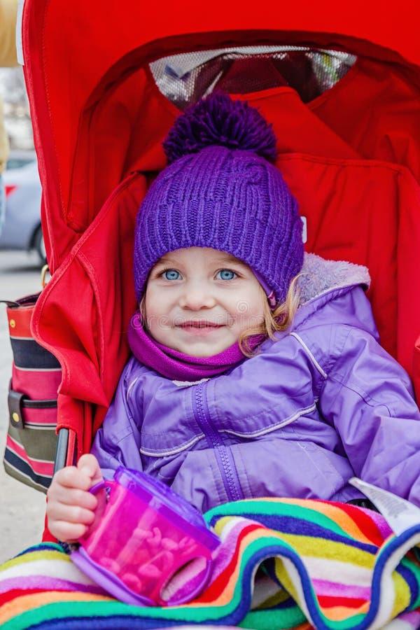 坐在婴儿推车的愉快的小女孩拿着有快餐的一个杯子 图库摄影