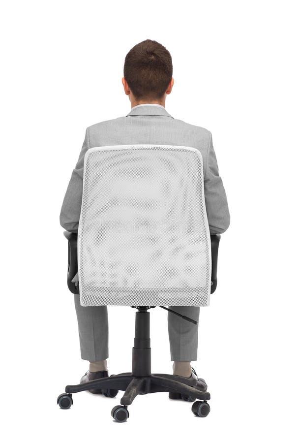 坐在从后面的办公室椅子的商人 免版税图库摄影