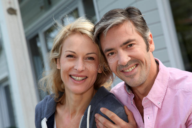 坐在围场的快乐的中年夫妇 免版税图库摄影