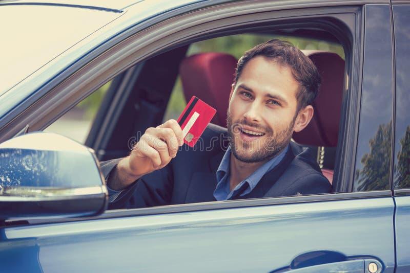 坐在他新的汽车里面的愉快的微笑的人显示信用卡 库存照片