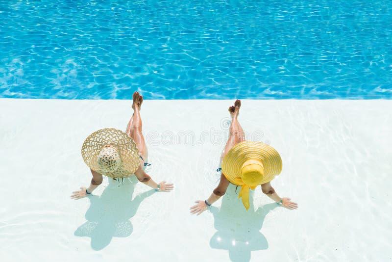 坐在水池边缘的帽子的妇女 免版税库存照片