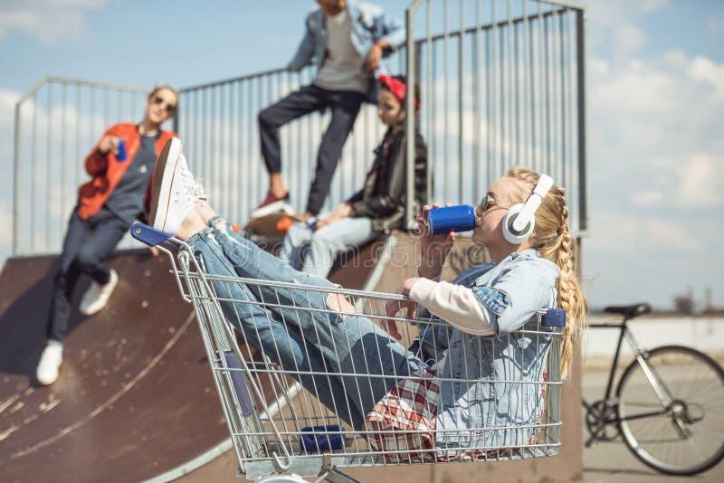 坐在购物车和喝从罐头的耳机的女孩,当获得的朋友乐趣在舷梯时 库存图片