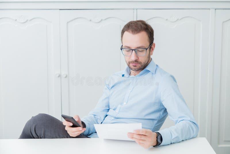 坐在他的书桌的商人,看纸张文件和h 免版税库存图片