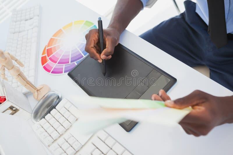 坐在他的书桌的设计师与数字化器一起使用 免版税库存照片