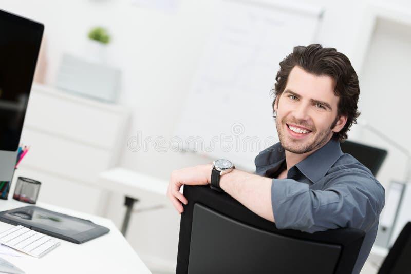 坐在他的办公室的微笑的年轻商人 免版税库存图片
