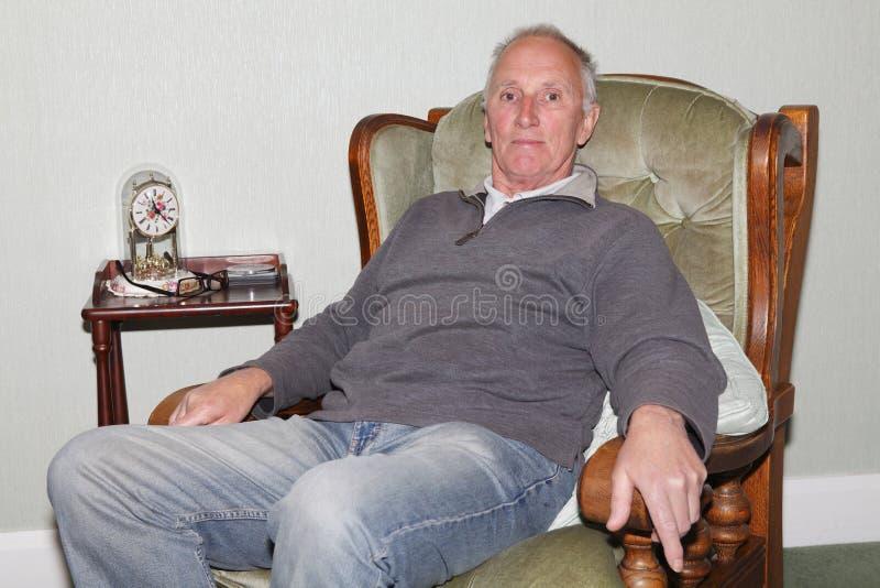 坐在他的扶手椅子的愉快的老人 免版税库存图片