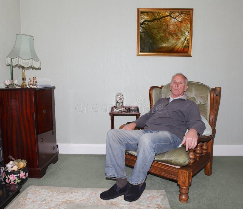 坐在他的扶手椅子的老人 免版税库存照片