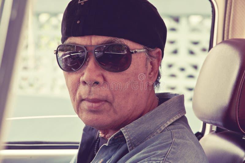 坐在他的汽车的老人 图库摄影