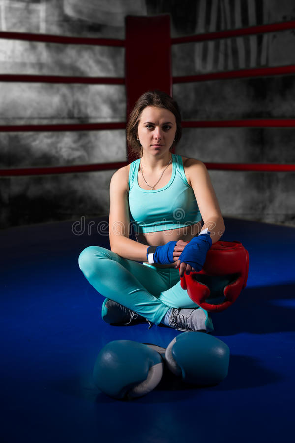 坐在说谎的拳击手套和helme附近的运动女性拳击手 库存照片