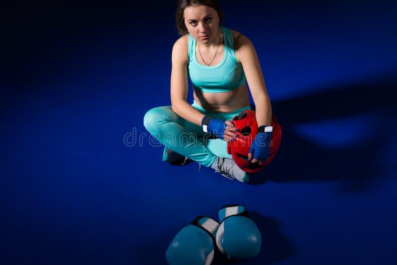 坐在说谎的拳击手套附近的年轻运动女性拳击手和 库存图片