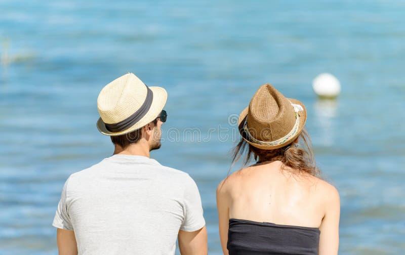 坐在水附近的夫妇 库存照片