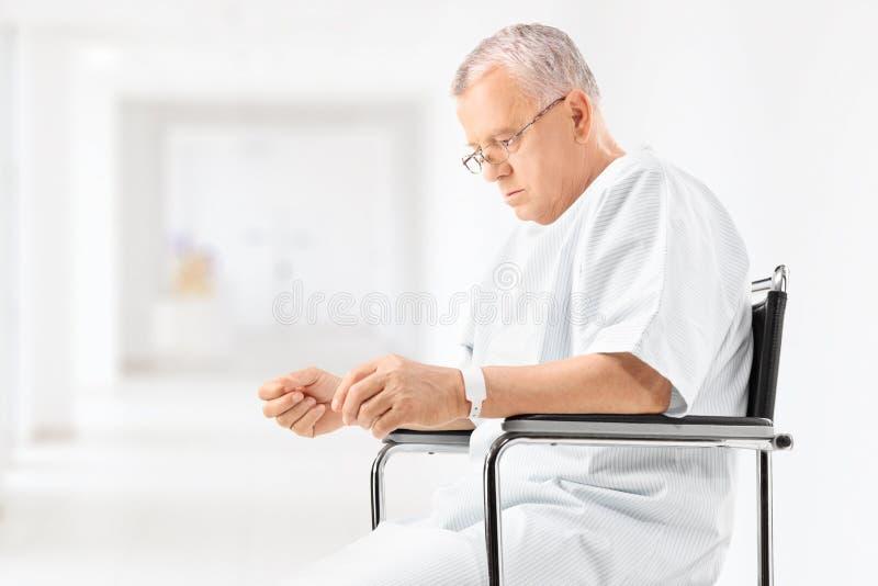 坐在医院走廊的担心的成熟患者 库存照片