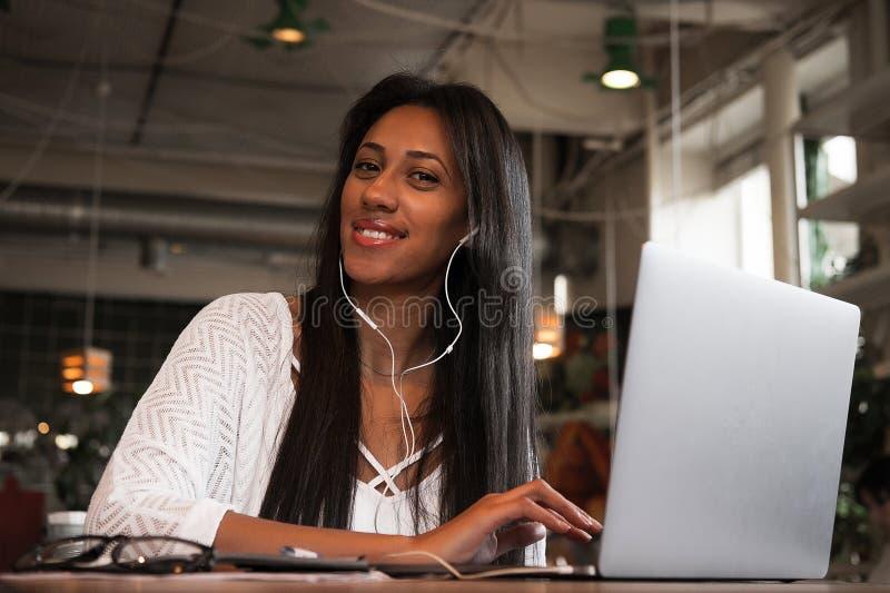 坐在caf的微笑的年轻非洲妇女特写镜头画象  免版税库存照片