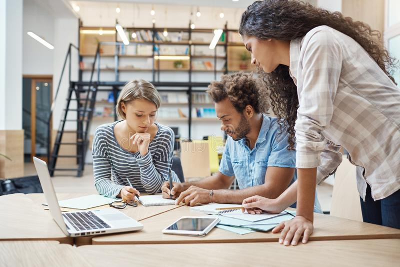 坐在coworking的空间的小组三个年轻不同种族的成功的商人,谈论新的项目  库存照片