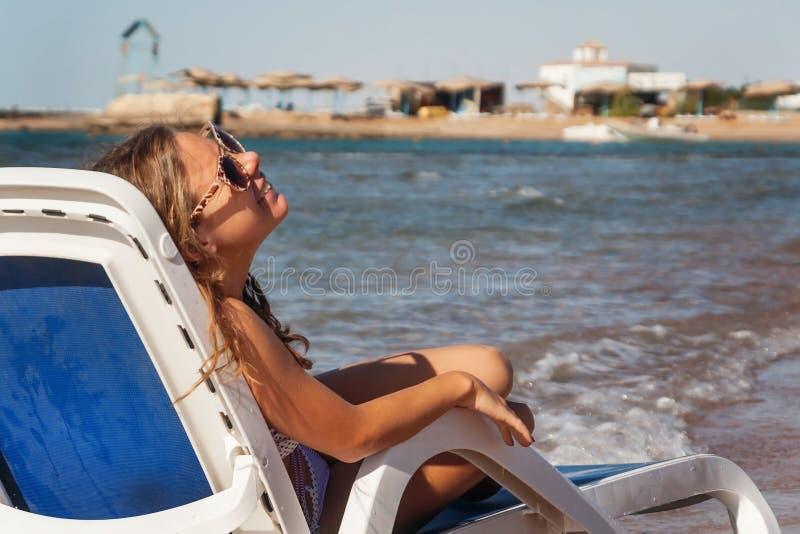坐在deckchair的太阳镜的笑的少妇,再 库存图片