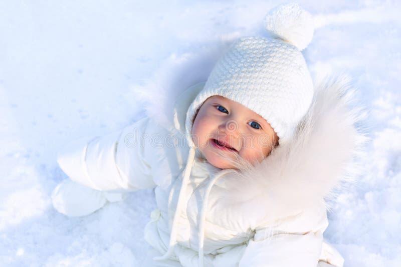 坐在fres的一个白色夹克和白色帽子的逗人喜爱的矮小的婴孩 免版税库存图片