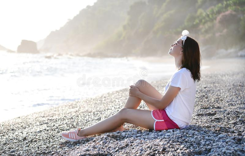 坐在Pebble海滩的年轻女人在陆间海 图库摄影