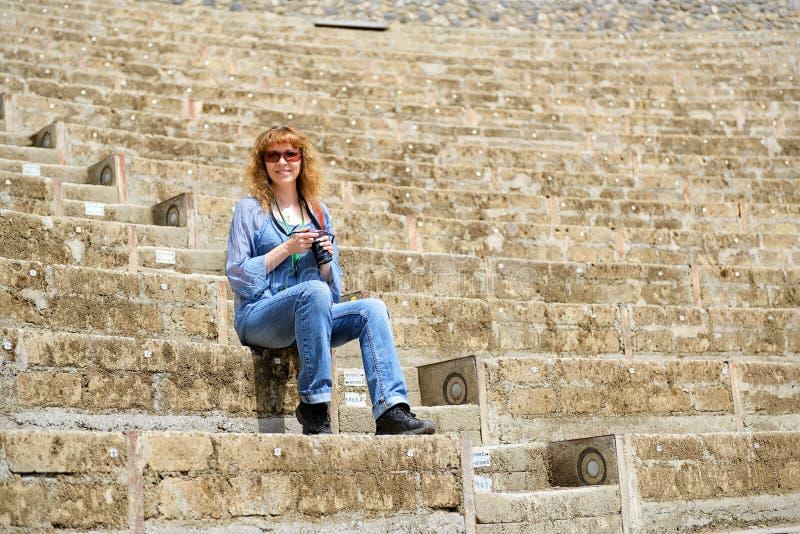 坐在Po的古老圆形剧场的一个年轻女性游人 库存照片