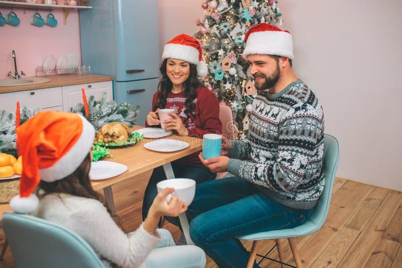 坐在tabel和神色的美丽的家庭的图片在彼此 他们在手上拿着杯子 人们互相微笑 图库摄影