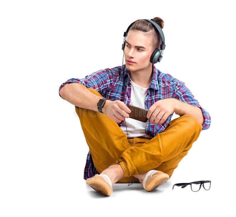 坐地板和享受音乐的年轻人 免版税库存图片