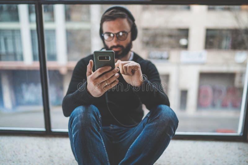 坐地板和使用手机的年轻有胡子的人为听的数字式音乐 水平 被弄脏的背景 图库摄影