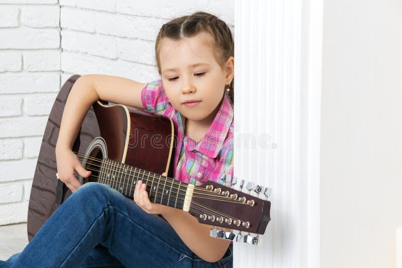 坐地板和弹吉他的小女孩 免版税库存照片