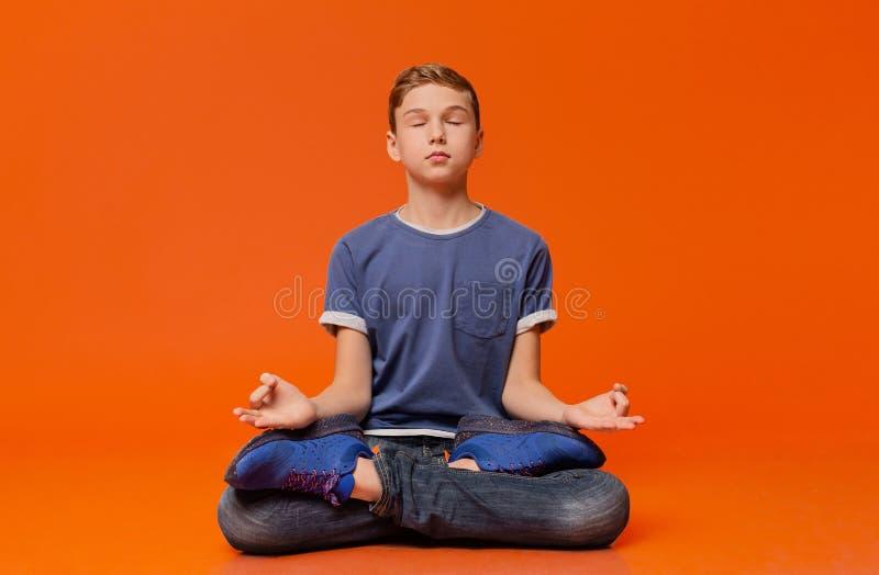 坐地板和思考在莲花坐的安静男孩 免版税库存照片