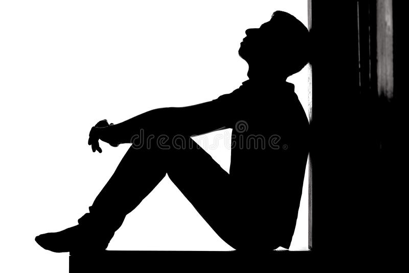 坐地板和查寻充满希望和绝望,消沉的人的一个年轻沉思人的档案在白色后面 免版税库存照片