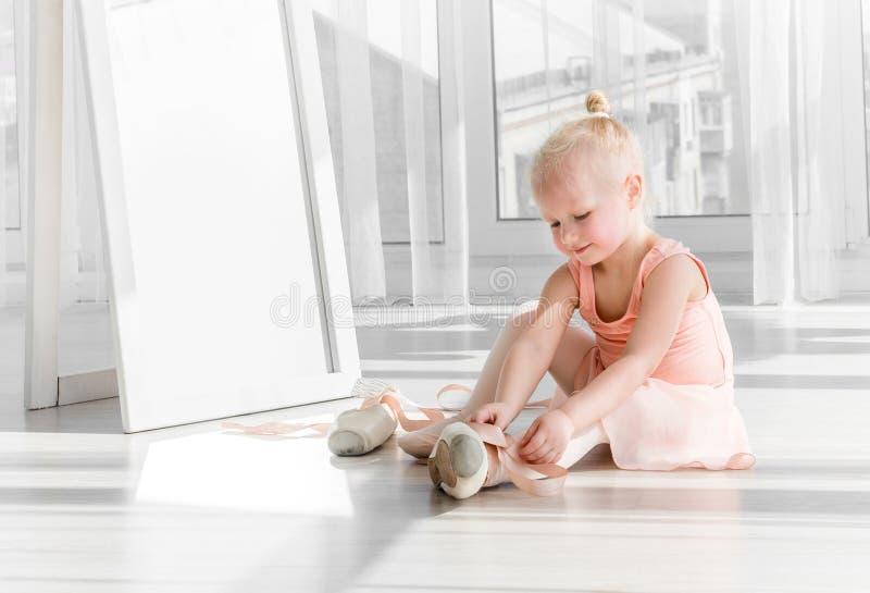 坐地板和栓芭蕾舞鞋的逗人喜爱的矮小的白肤金发的女孩 免版税库存照片