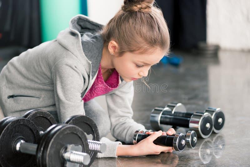 坐地板和看在健身房的运动服的小女孩哑铃 库存照片