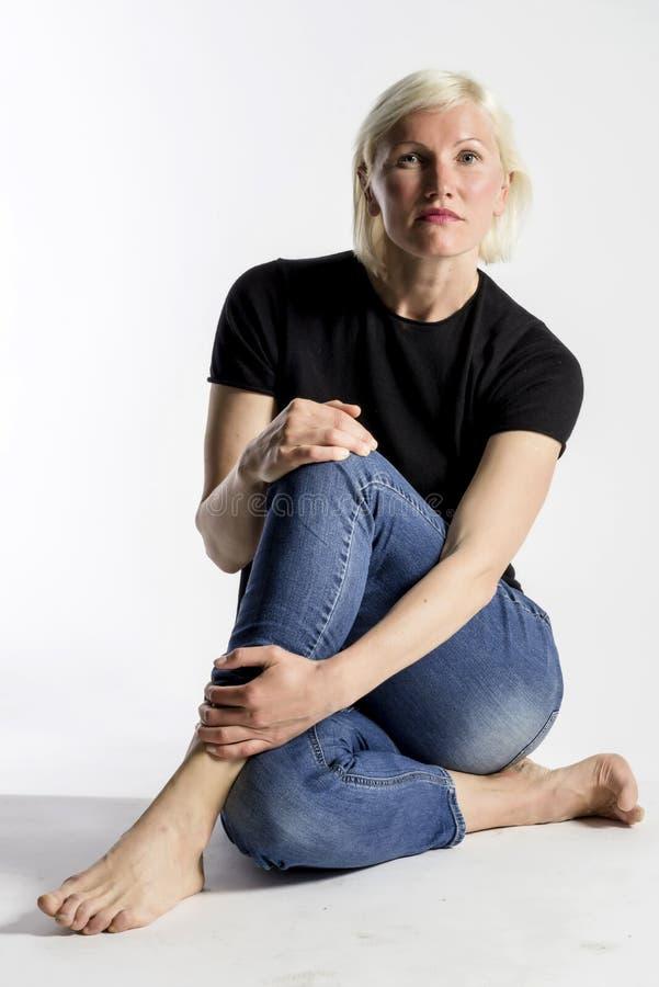 坐地板和看照相机的可爱的年轻白肤金发的妇女画象被隔绝在白色背景 免版税库存图片