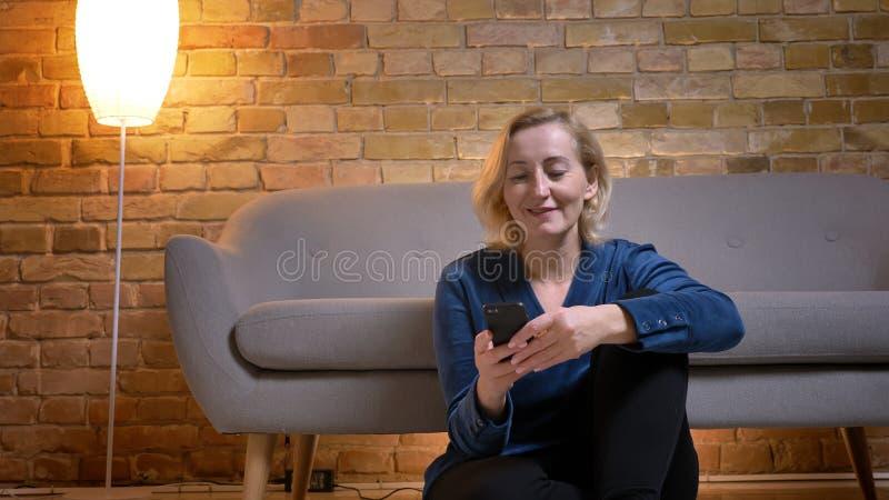坐地板和观看入在舒适家庭环境的智能手机的快乐的资深白种人夫人画象  库存图片