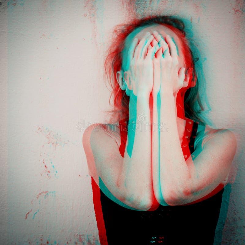 坐地板在墙壁附近和举行她的h的一名哀伤的妇女 库存照片