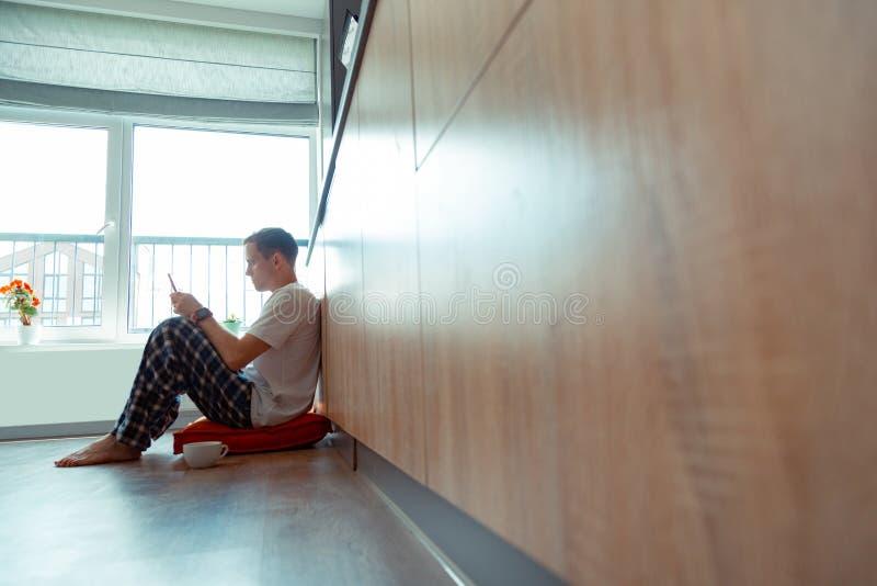 坐地板在窗口附近和读电子邮件的自由职业者 免版税库存图片